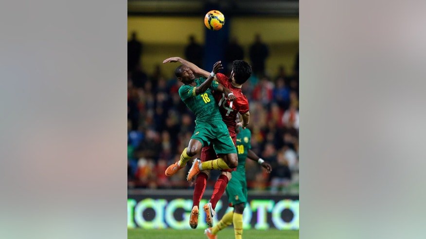 FILE - In this March 5 2014, file photo, Cameroon's Enoh Eyong, left, jumps for the ball with Portugal's Luis Neto during their friendly soccer match Wednesday, in Leiria, Portugal. The game is part of both teams' preparation for the World Cup in Brazil. (AP Photo/Armando Franca, File)