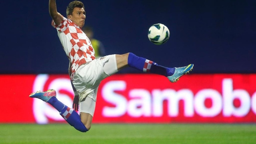 FILE - In this June 7, 2013, file photo, Croatia's Mario Mandzukic kicks the ball during the group A World Cup qualifying soccer match between Croatia and Scotland, in Zagreb, Croatia. Mandzukic, who was red-carded in a decisive qualifier against Iceland will have his suspension carried over from qualifying so he will have to sit out against the hosts. (AP Photo/Darko Bandic,File)