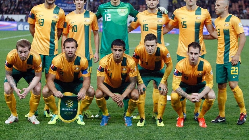 FILE - In this Oct. 11, 2013 file photo, Australia soccer team poses prior to the start their international soccer friendly match between France and Australia at the Parc Des Princes stadium in Paris, France. Background from left: Rhys Williams, Robbie Kruse, Mitchell Langerak, James Holland, Mile Jedinak and Mark Bresciano. Foreground from left: David Carney, Lucas Neill, Tim Cahill, Matty McKay and Luke Wilkshire. (AP Photo/Francois Mori, File)