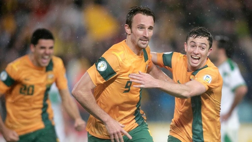 FILE - In this June 18, 2013, file photo, Australia's Josh Kennedy, center, celebrates with teammate Tommy Oar, right, after Kennedy scored against Iraq during their World Cup soccer Asian qualifying match at the Sydney Olympic Stadium in Sydney, Australia. Australia won one of its group games in South Africa four years ago, but will find it difficult to repeat that feat with an inexperienced squad that is being groomed for the 2018 World Cup in Russia. (AP Photo/Rick Rycroft)