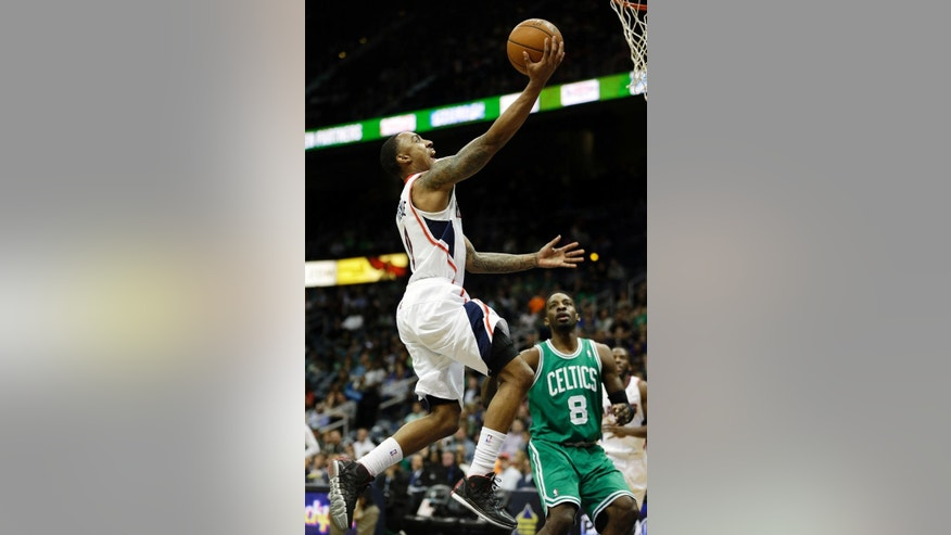 Atlanta Hawks' Jeff Teague, left, puts up a shot in front of Boston Celtics' Jeff Green in the first quarter of an NBA basketball game, Wednesday, April 9, 2014, in Atlanta. The Hawks won 105-97. (AP Photo/David Goldman)
