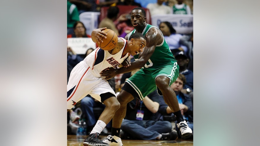 Atlanta Hawks' Jeff Teague, left, dribbles against Boston Celtics' Brandon Bass in the third quarter of an NBA basketball game, Wednesday, April 9, 2014, in Atlanta. The Hawks won 105-97. (AP Photo/David Goldman)