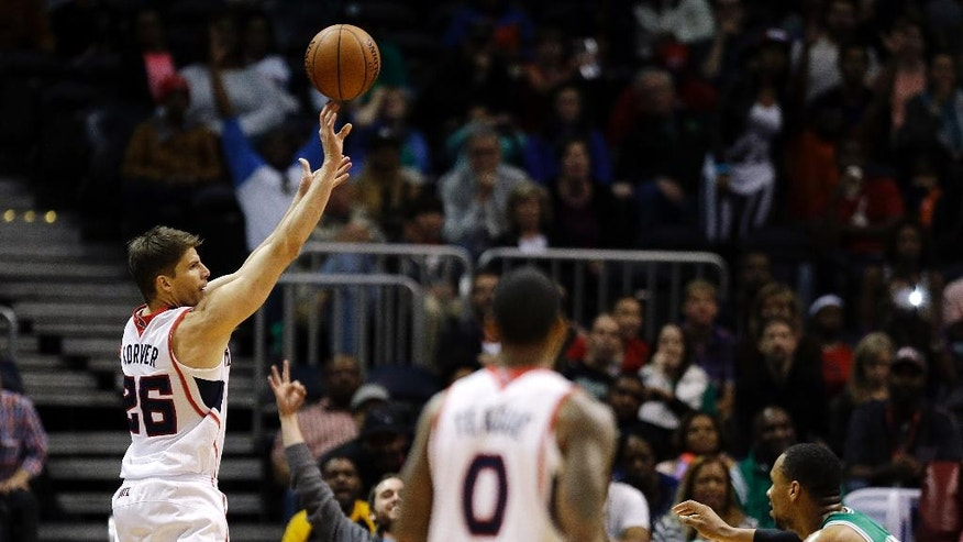 Atlanta Hawks' Kyle Korver, left, scores a 3-pointer in front of Boston Celtics' Jared Sullinger, right, late in the fourth quarter of an NBA basketball game, Wednesday, April 9, 2014, in Atlanta. The Hawks won 105-97. (AP Photo/David Goldman)