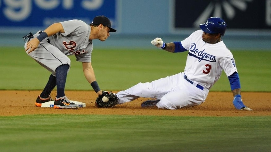 Detroit Tigers second baseman Ian Kinsler tags out Los Angeles Dodgers' Carl Crawford as he attempts to steal second base during the first inning of a baseball game in Los Angeles, Tuesday, April 8, 2014. (AP Photo/Kelvin Kuo)