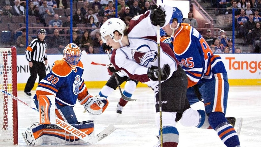 Colorado Avalanche's Nathan MacKinnon (29) and Edmonton Oilers' Martin Marincin (85) battle for the rebound as goalie Ben Scrivens (30) makes the save during first period NHL hockey action in Edmonton,  Alberta, on Tuesday April 8, 2014. (AP Photo/The Canadian Press, Jason Franson)