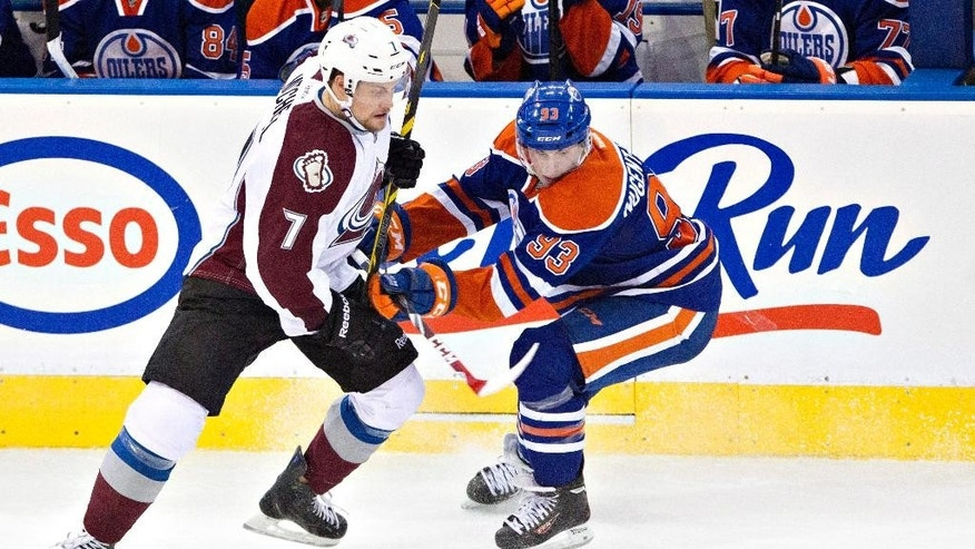 Colorado Avalanche's John Mitchell (7) is checked by Edmonton Oilers' Ryan Nugent-Hopkins (93) during second period NHL hockey action in Edmonton, Alberta, on Tuesday April 8, 2014. (AP Photo/The Canadian Press, Jason Franson)