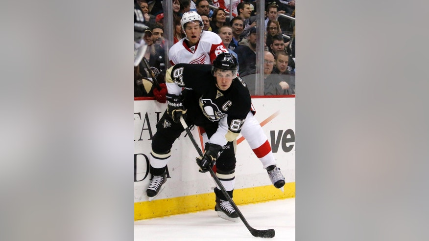 Pittsburgh Penguins' Sidney Crosby (87) collides with Detroit Red Wings' Danny DeKeyser (65) during the second period of an NHL hockey game in Pittsburgh, Wednesday, April 9, 2014. (AP Photo/Gene J. Puskar)