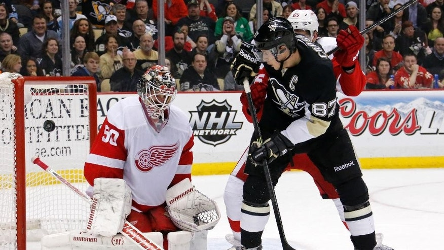 Pittsburgh Penguins' Sidney Crosby (87) can't get a shot past Detroit Red Wings goalie Jonas Gustavsson (50) and Red Wings' Danny DeKeyser, rear, during the second period of an NHL hockey game in Pittsburgh, Wednesday, April 9, 2014. (AP Photo/Gene J. Puskar)