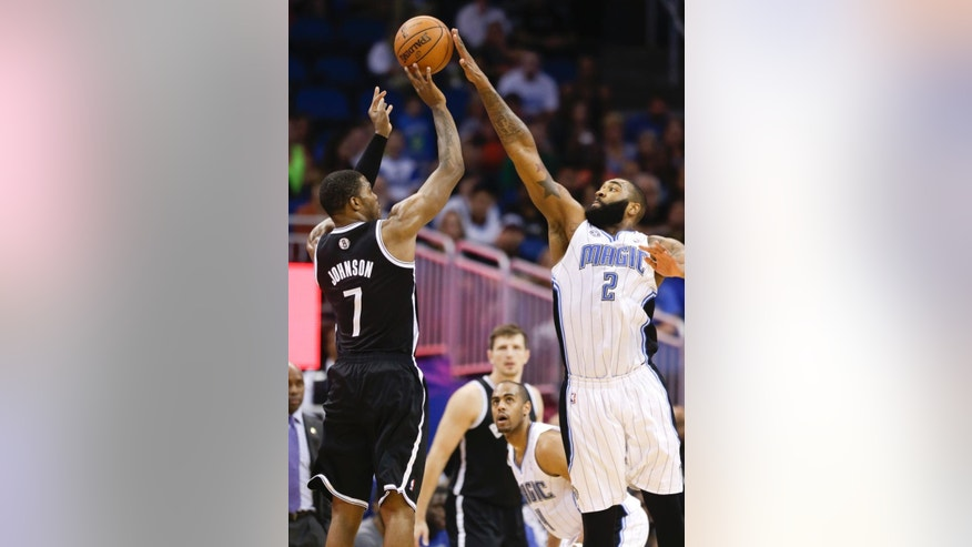 Orlando Magic's Kyle O'Quinn (2) blocks a shot by Brooklyn Nets' Joe Johnson (7) during the final seconds of an NBA basketball game in Orlando, Fla., Wednesday, April 9, 2014. Orlando won 115-111.(AP Photo/John Raoux)
