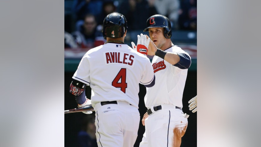 Cleveland Indians' Yan Gomes, right, congratulates Mike Aviles after Aviles hit a sacrifice fly off San Diego Padres starting pitcher Robbie Erlin in the third inning in the second game of the MLB baseball doubleheader, Wednesday, April 9, 2014, in Cleveland. Gomes scored on the play. (AP Photo/Tony Dejak)
