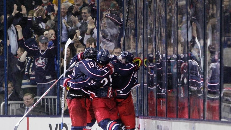 From left, Columbus Blue Jackets' Ryan Johansen, James Wisniewski and Boone Jenner celebrate Johansen's game-winning goal against the Phoenix Coyotes during the overtime period of an NHL hockey game Tuesday, April 8, 2014, in Columbus, Ohio. The Blue Jackets defeated the Coyotes 4-3 in overtime. (AP Photo/Jay LaPrete)