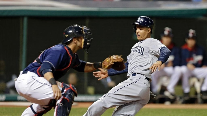 San Diego Padres' Will Venable slides past Cleveland Indians catcher Yan Gomes to score on a single by Jedd Gyorko in the sixth inning of the MLB baseball game Tuesday, April 8, 2014, in Cleveland. (AP Photo/Mark Duncan)