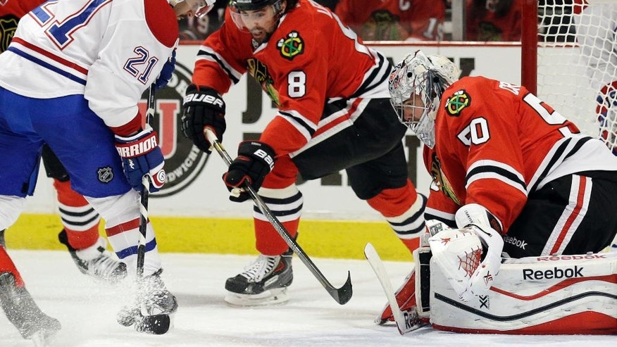 Montreal Canadiens' Brian Gionta (21) shoots against Chicago Blackhawks goalies Corey Crawford (50) during the first period of an NHL hockey game in Chicago, Wednesday, April 9, 2014. (AP Photo/Nam Y. Huh)