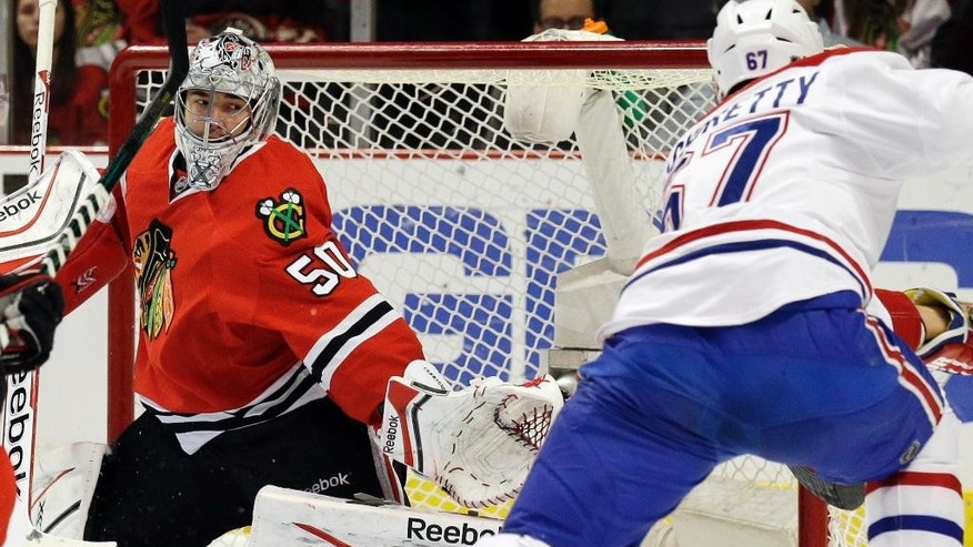 Chicago Blackhawks goalie Corey Crawford (50) blocks a shot by Montreal Canadiens' Max Pacioretty (67) during the first period of an NHL hockey game in Chicago, Wednesday, April 9, 2014. (AP Photo/Nam Y. Huh)