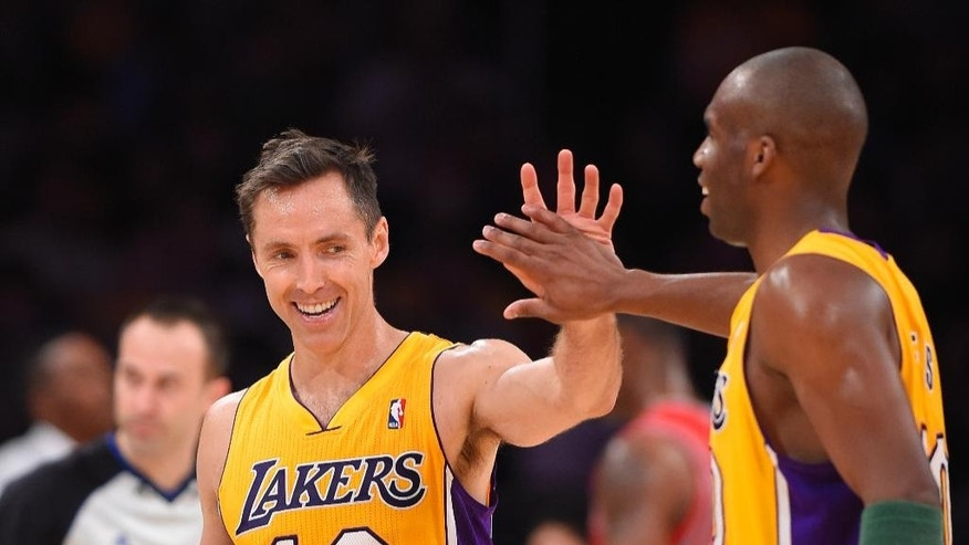 Los Angeles Lakers' Steve Nash, left, is congratulated by guard Jodie Meeks after Nash's assist to tie for third place in NBA career assists, during the first half of an NBA basketball game against the Houston Rockets, Tuesday, April 8, 2014, in Los Angeles. Meeks scored on the play. (AP Photo/Mark J. Terrill)