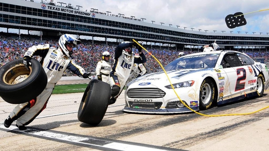 Brad Keselowski (2) gets tires during a pit stop during the NASCAR Sprint Cup series auto race at Texas Motor Speedway, Monday, April 7, 2014, in Fort Worth, Texas. (AP Photo/Ralph Lauer)