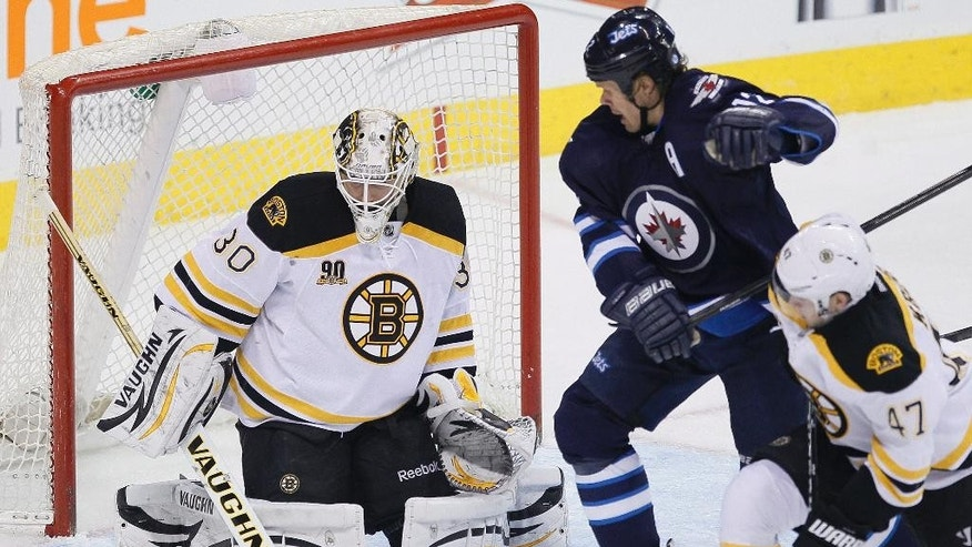 Boston Bruins goaltender Chad Johnson (30) saves a shot as Winnipeg Jets' Olli Jokinen (12) and Bruins' Torey Krug (47) look for a rebound during the first period of an NHL hockey game Thursday, April 10, 2014, in Winnipeg, Manitoba. (AP Photo/The Canadian Press, John Woods)