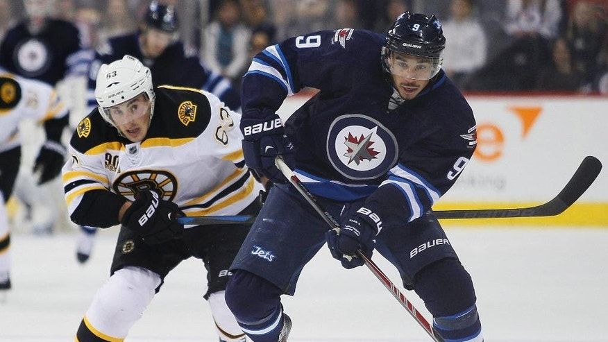 Boston Bruins' Brad Marchand (63) chases down Winnipeg Jets' Evander Kane (9) during the second period of an NHL hockey game Thursday, April 10, 2014, in Winnipeg, Manitoba. (AP Photo/The Canadian Press, John Woods)
