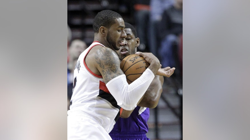 Portland Trail Blazers forward LaMarcus Aldridge, left, fights to drive inside against Sacramento Kings forward Jason Thompson during the first half of an NBA basketball game in Portland, Ore., Wednesday, April 9, 2014. (AP Photo/Don Ryan)