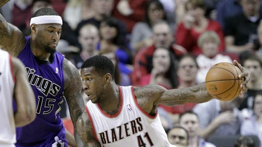 Portland Trail Blazers forward Thomas Robinson, right, drives against Sacramento Kings center DeMarcus Cousins during the first half of an NBA basketball game in Portland, Ore., Wednesday, April 9, 2014. (AP Photo/Don Ryan)