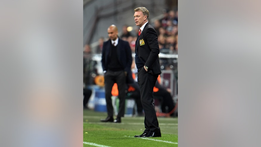 Manchester United's manager David Moyes, right, and Bayern head coach Pep Guardiola of Spain, left, attend the Champions League quarterfinal second leg soccer match between Bayern Munich and Manchester United in the Allianz Arena in Munich, Germany, Wednesday, April 9, 2014. (AP Photo/Kerstin Joensson)
