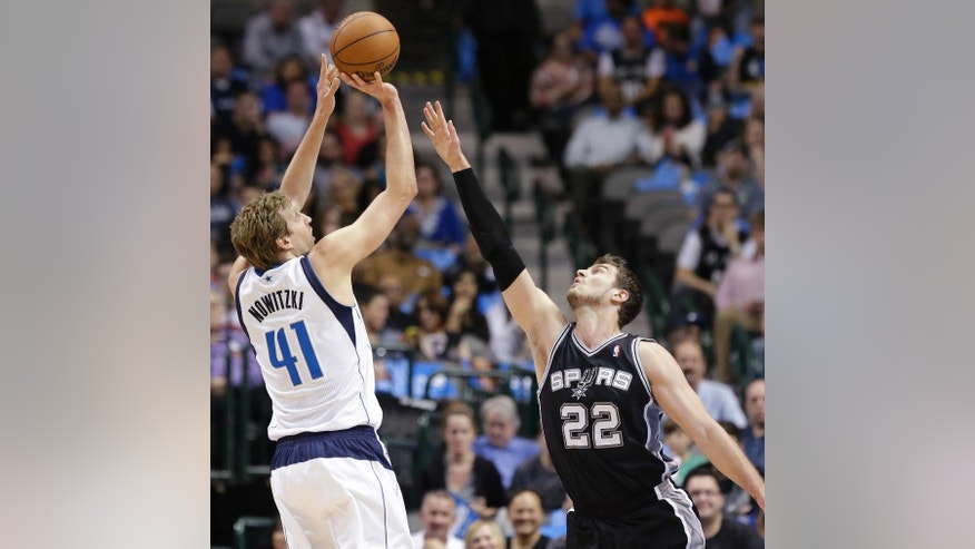 Dallas Mavericks forward Dirk Nowitzki (41) shoots against San Antonio Spurs center Tiago Splitter during the first half an NBA basketball game Thursday, April 10, 2014, in Dallas. (AP Photo/LM Otero)