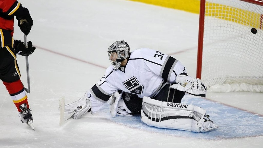 Calgary Flames' Sean Monahan, left, scores past Los Angeles Kings goalie Jonathan Quick during the shootout of an NHL hockey game in Calgary, Alberta, Wednesday, April 9, 2014. (AP Photo/The Canadian Press, Larry MacDougal)