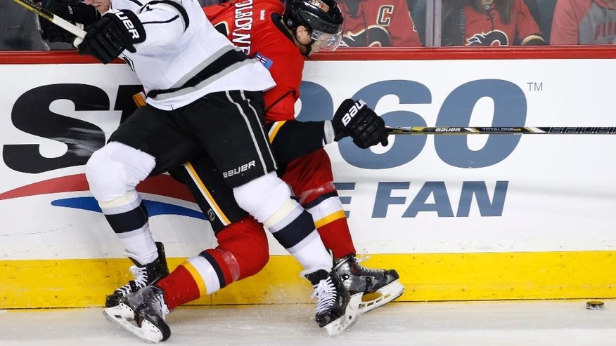 Los Angeles Kings' Matt Greene, left, battles for the puck with Calgary Flames' Joe Colborne during first period NHL action in Calgary, Alta., Wednesday, April 9, 2014. (AP Photo/The Canadian Press, Larry MacDougal)