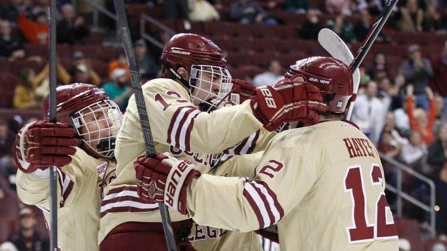 Boston College's Johnny Gaudreau, center, jumps into the arms of teammate Kevin Hayes, right, after scoring a goal during the first period of an NCAA men's college hockey Frozen Four tournament game against Union, Thursday, April 10, 2014, in Philadelphia. (AP Photo/Chris Szagola)