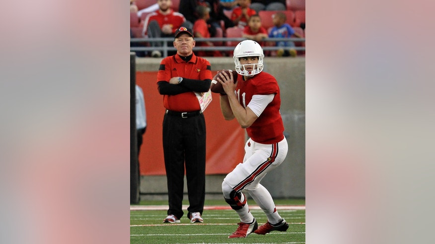 Louisville quarterback Will Gardner (11) drops back to pass as head coach Bobby Petrino watches in the background during a NCAA college spring football game in Louisville, Ky., Friday, April 11, 2014.  (AP Photo/Garry Jones)