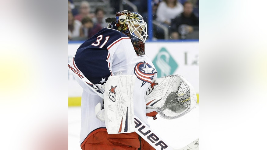 Columbus Blue Jackets goalie Curtis McElhinney (31) takes a shot by Tampa Bay Lightning defenseman Eric Brewer off the face mask during the second period of an NHL hockey game Friday, April 11, 2014, in Tampa, Fla. Brewer scored on the shot. (AP Photo/Chris O'Meara)