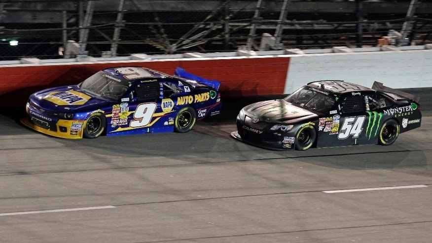 Chase Elliott (9) leads Kyle Busch (54) during a NASCAR Nationwide series auto race at Darlington Speedway in Darlington, S.C., Friday, April 11, 2014. (AP Photo/Chuck Burton)