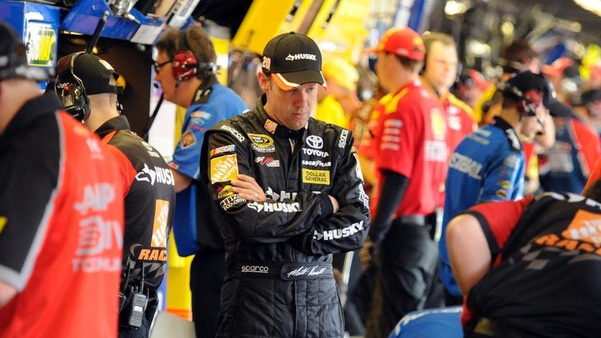 Matt Kenseth looks at his race car as his crew works during a NASCAR Sprint Cup series auto race practice at Darlington Speedway in Darlington, S.C., Friday, April 11, 2014. (AP Photo/Mike McCarn)