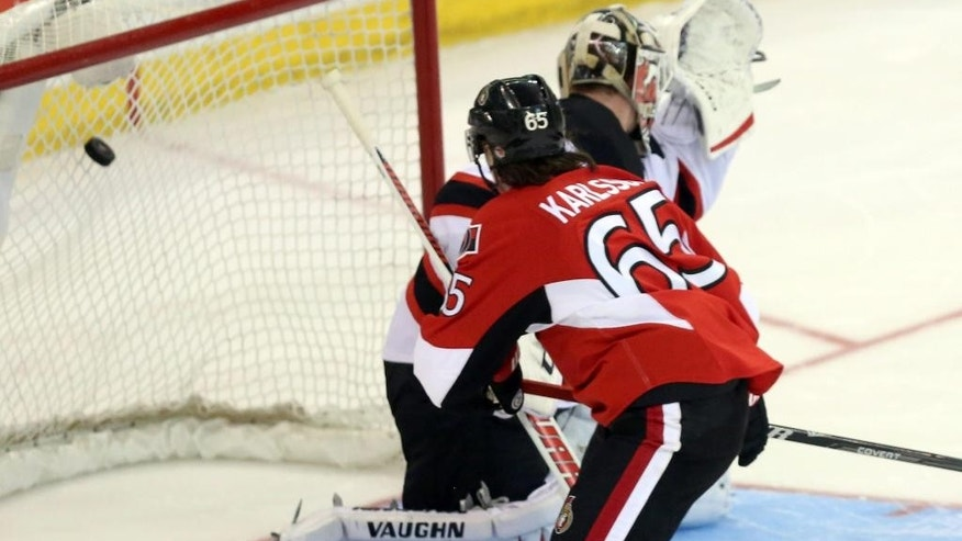 Ottawa Senators' Erik Karlsson (65) score against New Jersey Devils goaltender Cory Schneider in a shootout during NHL hockey game action in Ottawa, Ontario, Thursday, April 10, 2014. The Senators won 2-1. (AP Photo/The Canadian Press, Fred Chartrand)