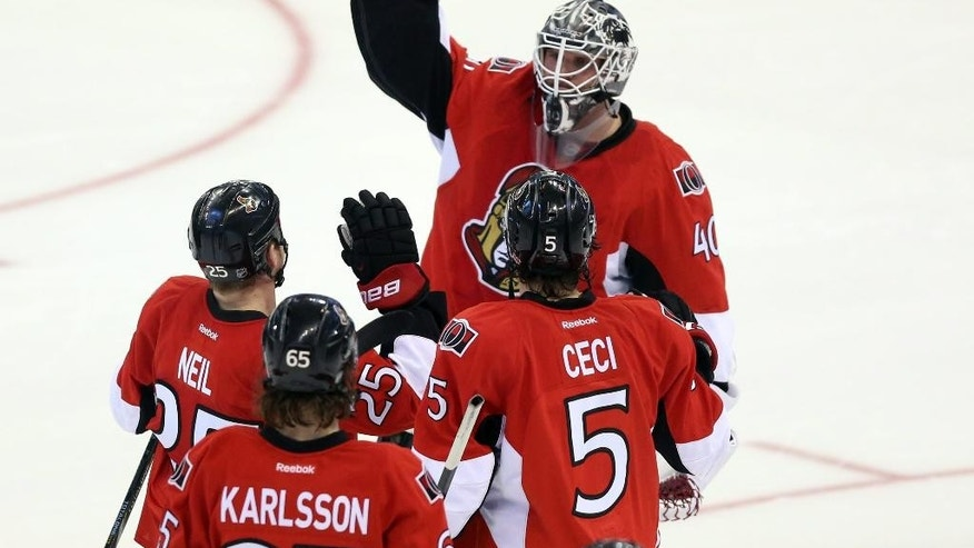 Ottawa Senators goaltender Robin Lehner (40) celebrates with teammates after they defeated the New Jersey Devils 2-1 in a shootout during NHL hockey game action in Ottawa, Ontario, Thursday, April 10, 2014. (AP Photo/The Canadian Press, Fred Chartrand)