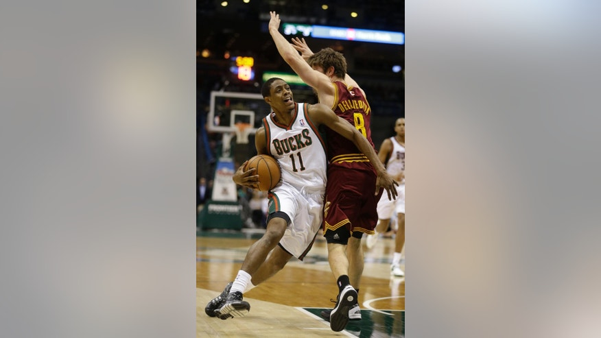 Milwaukee Bucks' Brandon Knight (11) drives against Cleveland Cavaliers' Matthew Dellavedova (8) during the second half of an NBA basketball game Friday, April 11, 2014, in Milwaukee. (AP Photo/Jeffrey Phelps)