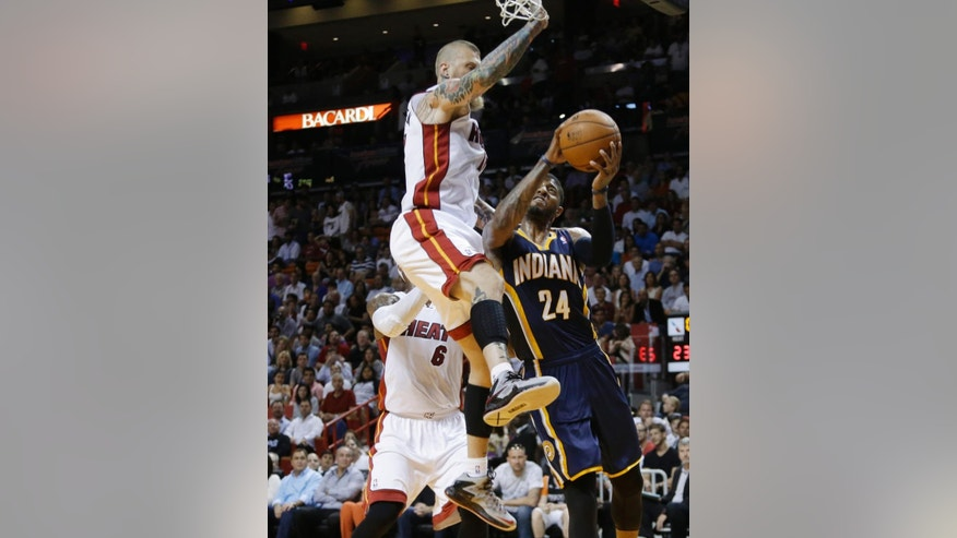 Indiana Pacers' Paul George (24) looks to the basket before being fouled by Miami Heat's Chris Andersen, top, during the first half of an NBA basketball game, Friday, April 11, 2014, in Miami. (AP Photo/Lynne Sladky)