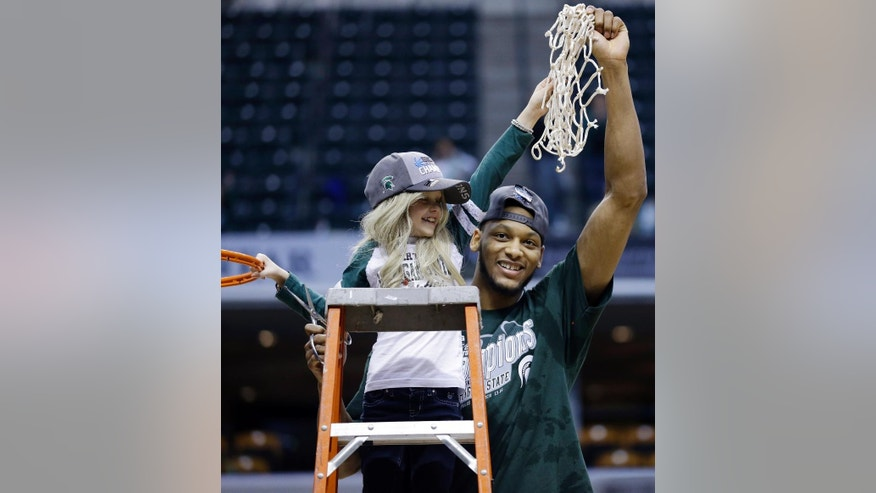"FILE - In this March 16, 2014 file photo, Michigan State forward Adreian Payne, right, hoists the net with Lacey Holsworth, who is battling cancer, after Michigan State defeated Michigan 69-55 in an NCAA college basketball game in the championship of the Big Ten Conference tournament in Indianapolis. The father of  8-year-old Lacey Holsworth, who befriended Michigan State basketball star Adreian Payne says his daughter has died. Matt Holsworth says Lacey Holsworth died at their St. Johns, Mich., home late Tuesday, April 8, 2014 ""with her mommy and daddy holding her in their arms."" (AP Photo/Michael Conroy, File)"