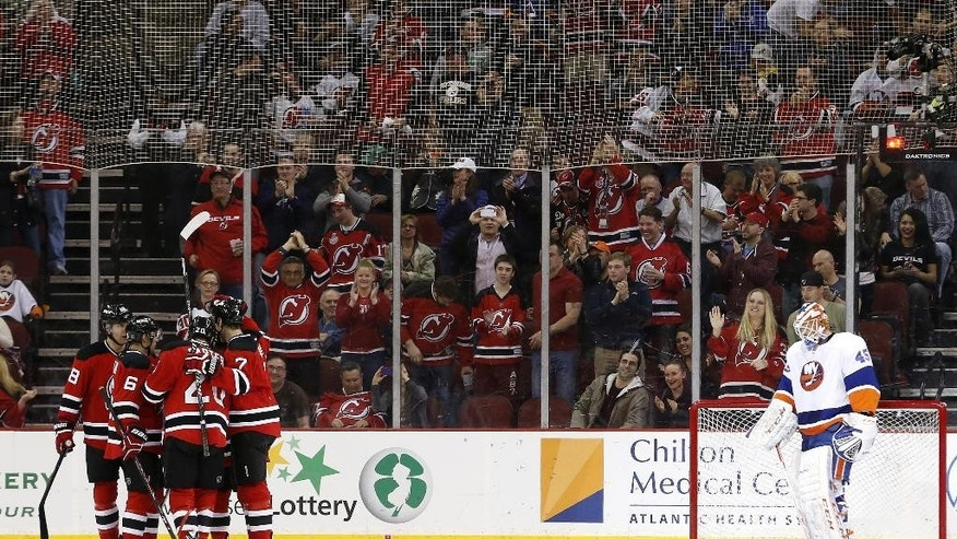 New Jersey Devils players, left, celebrate a goal by center Ryan Carter as New York Islanders goalie Anders Nilsson, of Sweden, stands in front of his net during the first period of an NHL hockey game on Friday, April 11, 2014, in Newark, N.J. (AP Photo/Julio Cortez)