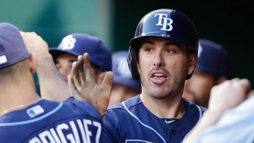 Tampa Bay Rays' Matt Joyce, right, is congratulated in the dugout after hitting a solo home run off Cincinnati Reds starting pitcher Johnny Cueto in the third inning of a baseball game, Friday, April 11, 2014, in Cincinnati. (AP Photo/Al Behrman)