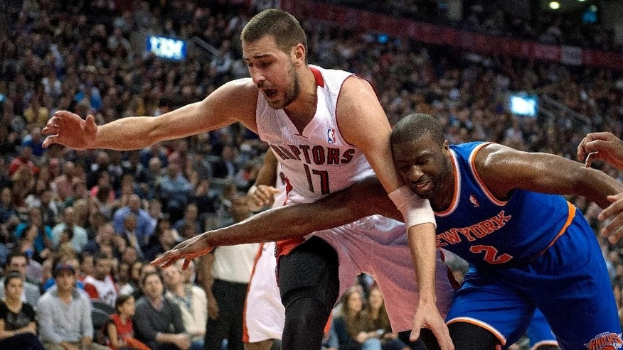 Toronto Raptors center Jonas Valanciunas (17) and New York Knicks guard Raymond Felton (2) chase down a loose ball during the first half of an NBA basketball game Friday, April 11, 2014, in Toronto. (AP Photo/The Canadian Press, Frank Gunn)