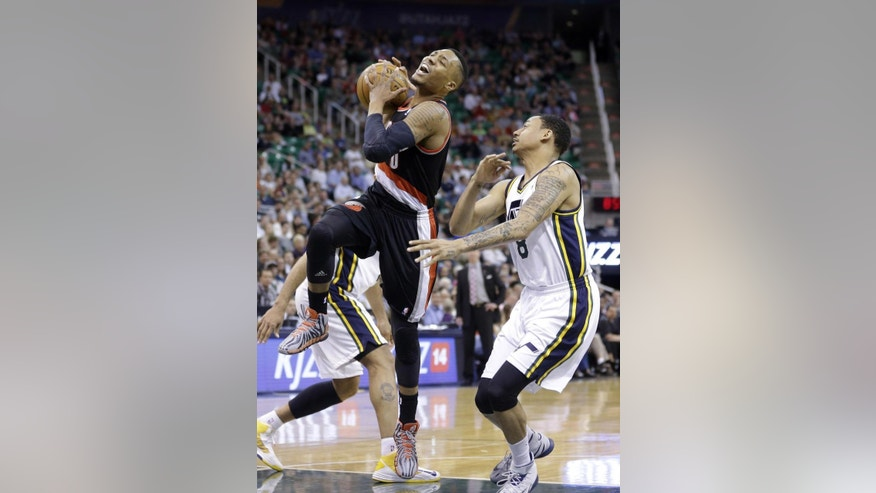 Portland Trail Blazers' Damian Lillard (0) goes to the basket as Utah Jazz's Diante Garrett (8) defends in the fourth quarter during an NBA basketball game on Friday, April 11, 2014, in Salt Lake City. The Trail Blazers won 111-99. (AP Photo/Rick Bowmer)