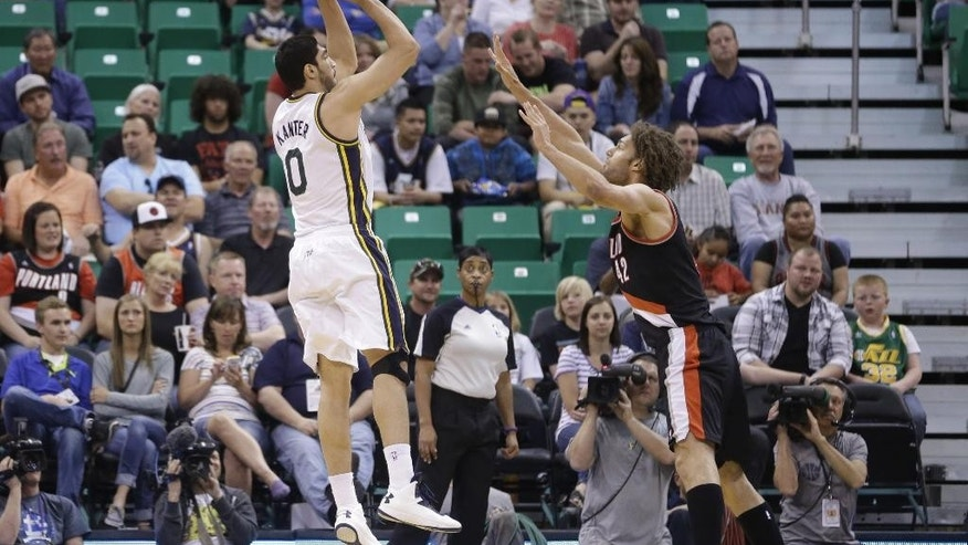 Utah Jazz's Enes Kanter (0) shoots as Portland Trail Blazers' Robin Lopez (42) defends in the first quarter during an NBA basketball game on Friday, April 11, 2014, in Salt Lake City. (AP Photo/Rick Bowmer)
