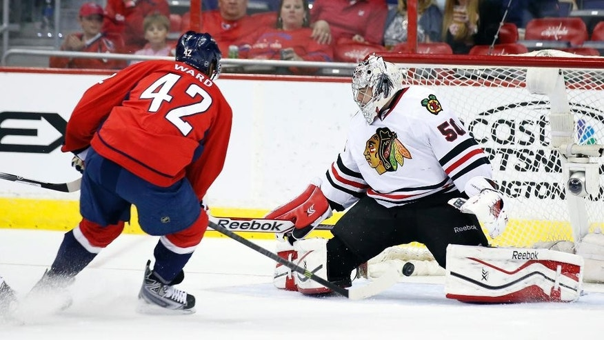 Washington Capitals right wing Joel Ward (42) misses a shot between the legs of Chicago Blackhawks goalie Corey Crawford (50) in the first period of an NHL hockey game, Friday, April 11, 2014, in Washington. (AP Photo/Alex Brandon)
