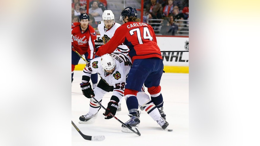 Chicago Blackhawks left wing Brandon Bollig (52) reaches for the puck as Washington Capitals defenseman John Carlson (74) defends, in the first period of an NHL hockey game, Friday, April 11, 2014, in Washington. (AP Photo/Alex Brandon)
