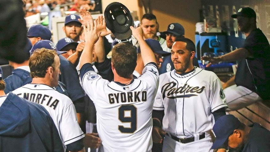 San Diego Padres' Jedd Gyorko is congratulated by teammates after scoring and driving in a run against the Detroit Tigers during the first inning of a baseball game Friday, April 11, 2014, in San Diego. (AP Photo/Lenny Ignelzi)