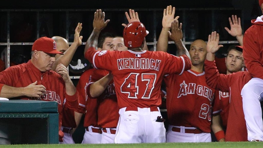 Los Angeles Angels' Howie Kendrick, center, is greeted by teammates after he scored on a single hit by Chris Iannetta during the second inning of a baseball game against the New York Mets, Friday, April 11, 2014, in Anaheim, Calif. (AP Photo/Jae C. Hong)