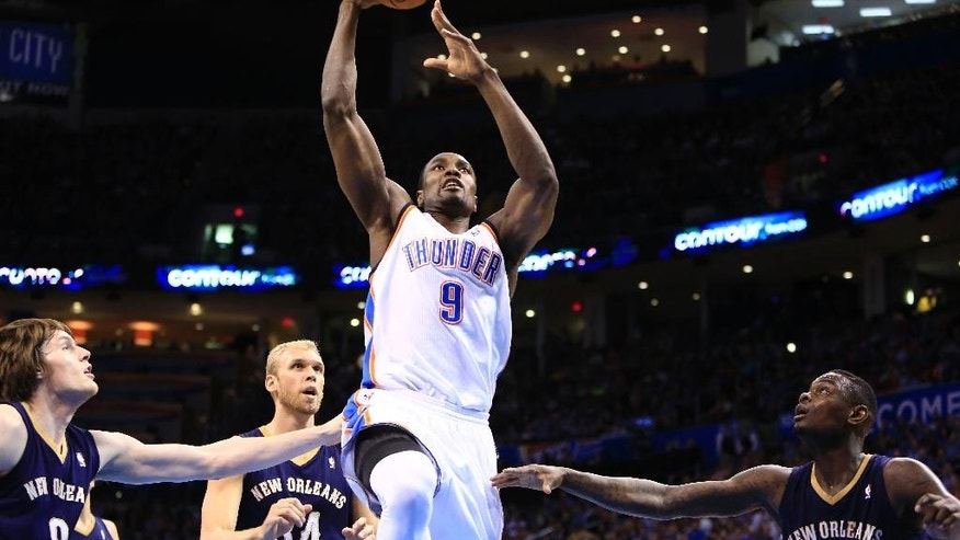 Oklahoma City Thunder forward Serge Ibaka (9) goes to the basket in front of New Orleans Pelicans forward Luke Babbitt (8), New Orleans Pelicans center Greg Stiemsma (34) during the second quarter of a NBA basketball game in Oklahoma City, Friday, April 11, 2014. (AP Photo/Alonzo Adams)