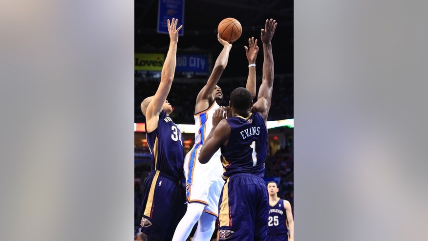 Oklahoma City Thunder forward Kevin Durant (35) goes to the basket between New Orleans Pelicans center Greg Stiemsma (34) and New Orleans Pelicans forward Tyreke Evans (1) during the second quarter of a NBA basketball game in Oklahoma City, Friday, April 11, 2014. (AP Photo/Alonzo Adams)