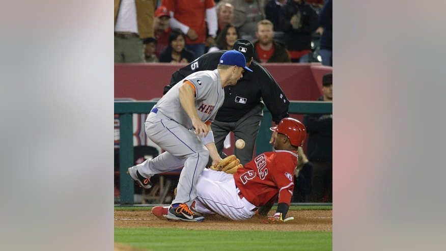 Los Angeles Angels' Erick Aybar advances to third on a single by Kole Calhoun as New York Mets third baseman David Wright misses the throw during the eighth inning of a baseball game Friday, April 11, 2014, in Anaheim, Calif. (AP Photo/Jae C. Hong)